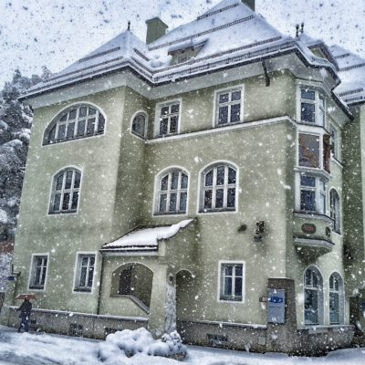 Big stone house with many windows and snow falling all around