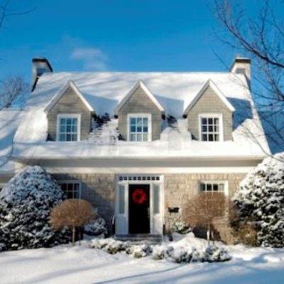 Brick home with red front door and three dormers with snow on top and in the yard talking about replacement windows with Paul Henry's Windows