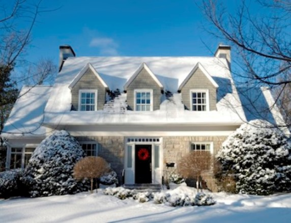 Beautiful snow covered home with dormer widows and snow covered bushes outside