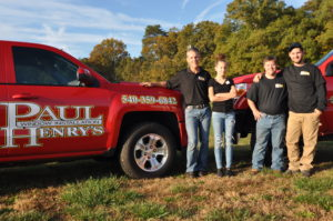 Four people standing nest top a red Paul Henry's Windows truck