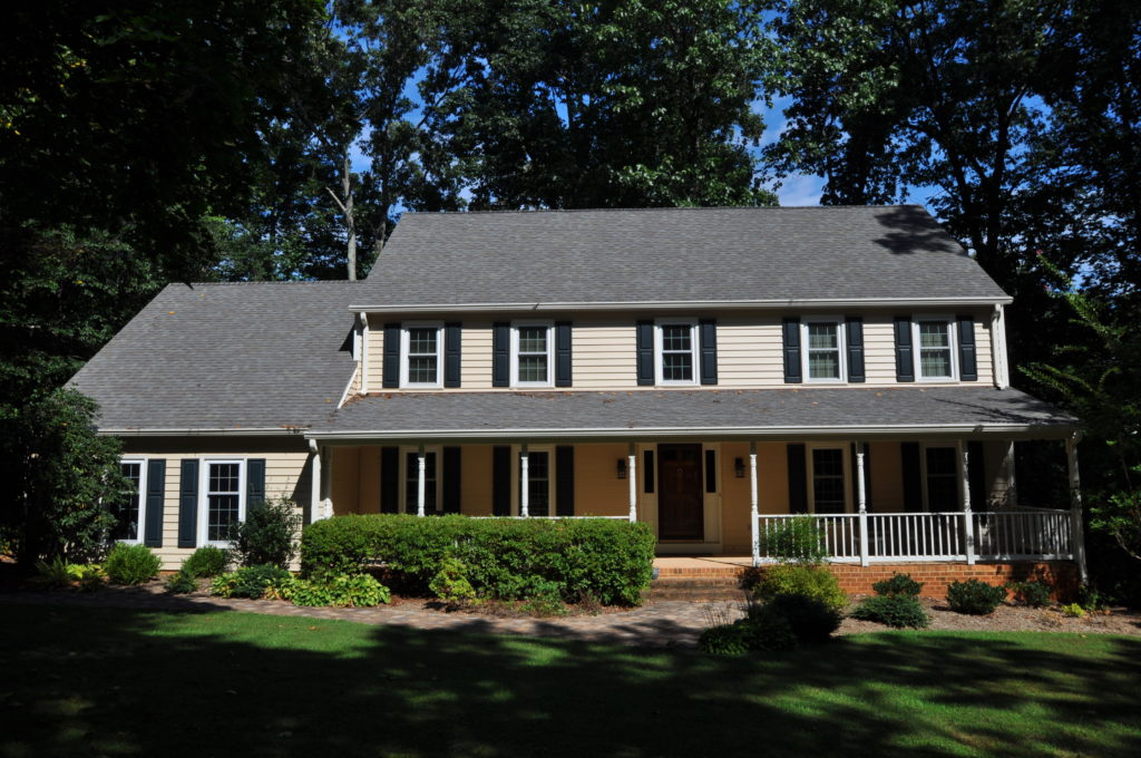 Customer's house after Paul Henry's Windows Installation rep;aced the tan siding and the shutters.